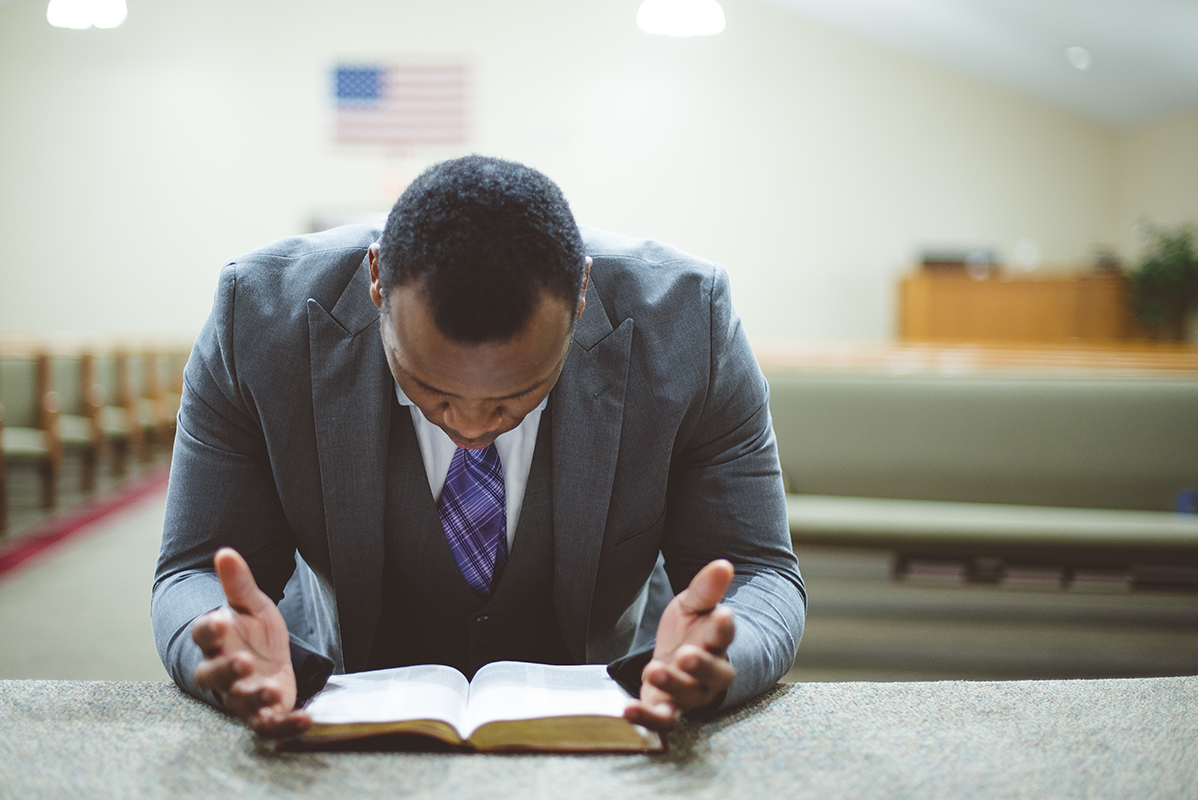 Pastor Praying Over Bible Resized